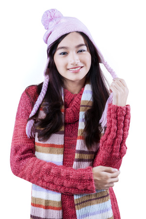 Beautiful high school student smiling joy while wearing knitted clothes for winter, isolated on white photo