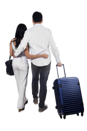 carrying: Young couple going to travel while carrying luggage, isolated over white background