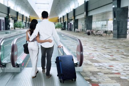 비행: 공항 홀에서 수하물을 운반하는 동안 에스컬레이터에서 걷는 두 사람