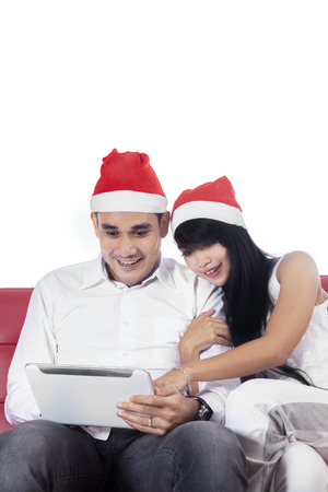 Portrait of couple sitting on sofa and wearing christmas hat while using a digital tablet, isolated on white photo