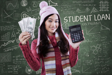 education loan: Portrait of beautiful female student wearing winter clothes and holding money with calculator in class