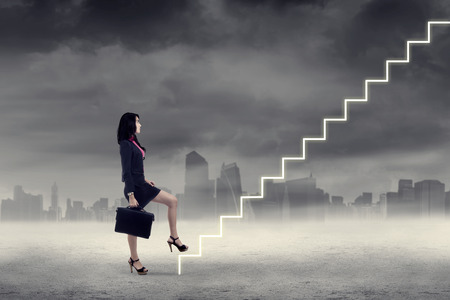 up stair: Businesswoman walking up on stairs in cloudy weather Stock Photo