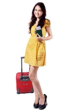 Portrait of pretty girl standing in studio while pulling a luggage and holding passport, isolated on white photo