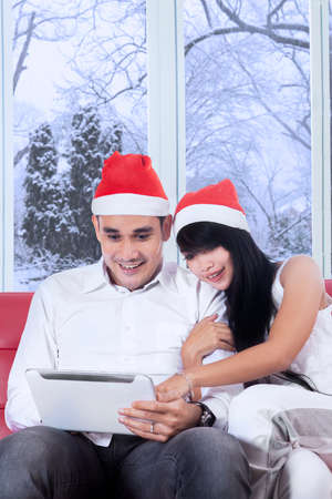 Portrait of happy couple wearing christmas hat, using a digital tablet on sofa with winter background on the window photo