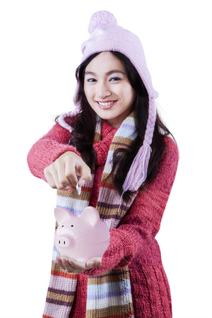 Portrait of a beautiful girl wearing winter clothes holding a piggybank and put a coin photo