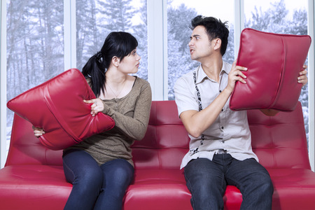relationship problems: Portrait of young couple quarreling at home and throwing pillows to each other, shot in winter day