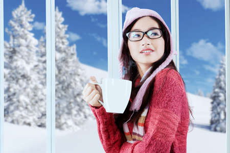 Pretty girl wearing knitted clothes and hat, enjoying a cup of hot coffee at home photo