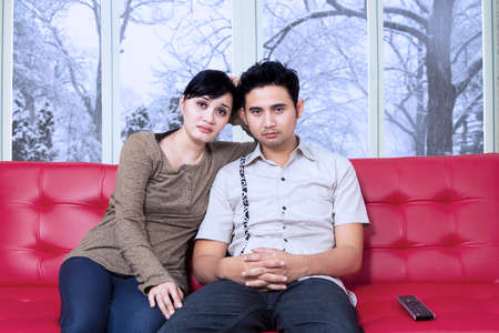 Portrait of young couple sitting on sofa and watching television together with bored expression photo