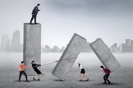 fussy: Male entrepreneur standing on the top and yelling to his workers for working harder