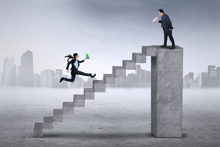 subordinate: Young entrepreneur standing on the bar and using a megaphone to command his subordinate Stock Photo