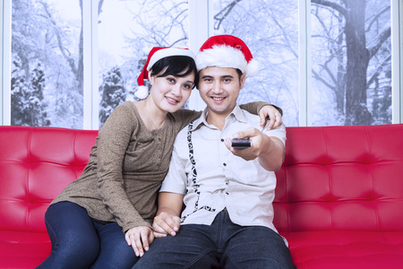 christmas movies: Portrait of asian couple sitting on sofa and wearing christmas hat, watching tv together with winter background on the window