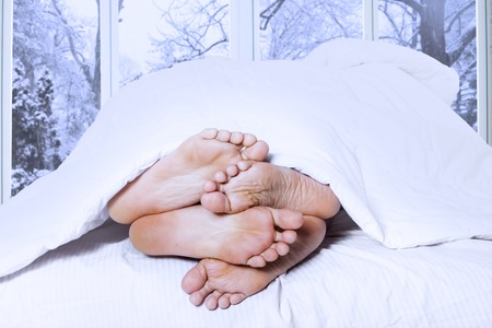 Affectionate of couple sleeping on the bedroom looks from their feet, shot in winter day Stock Photo