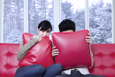 Portrait of scared couple watching horror movie at home and hiding on the pillows photo