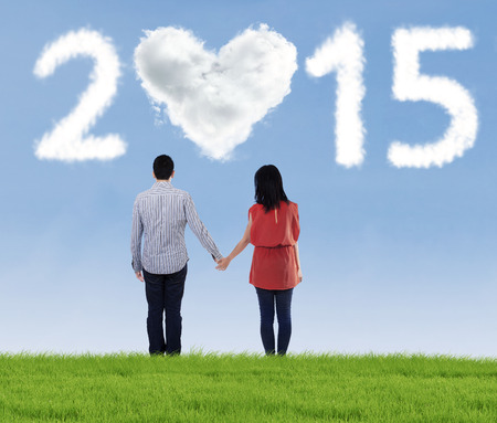 under heart: Rear view of young couple standing and holding hands on the meadow under heart cloud shaped 2015