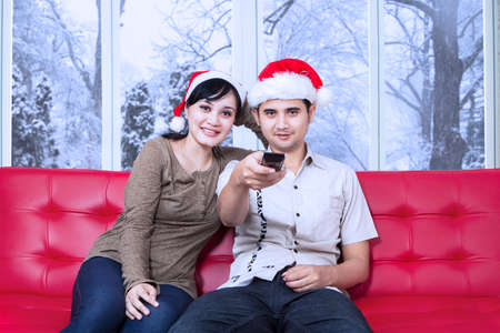 christmas movies: Christmas couple sitting on sofa and watching tv together while the man holds the remote control