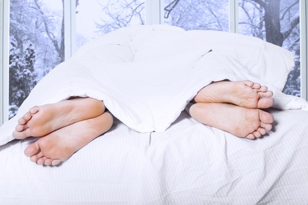 woman sex: Couple feet sleeping separately on the bedroom, symbolizing couple having family problem