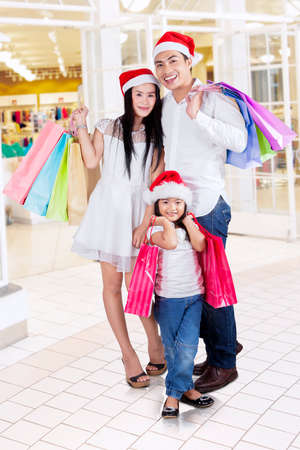 Happy family standing in the mall while carrying shopping bags photo