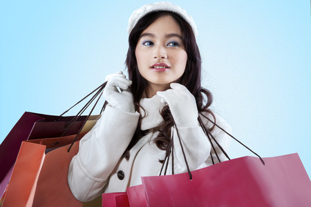 love: Attractive woman with beautiful face wearing winter clothes, holding shopping bags ove blue background