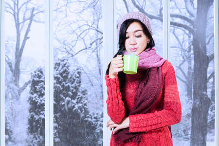 Portrait beautiful girl wearing winter clothes and blow a warm drink at home with winter background on the window photo