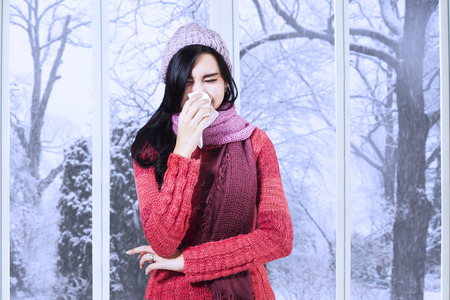 Young girl having flu and blowing her nose at handkerchief, shot at home in winter day photo