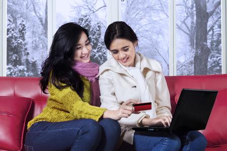 ropa de invierno: Retrato de dos mujeres jóvenes vistiendo ropa de abrigo, usando la computadora portátil y una tarjeta de crédito para compras en línea en el sofá en vacaciones de invierno Foto de archivo