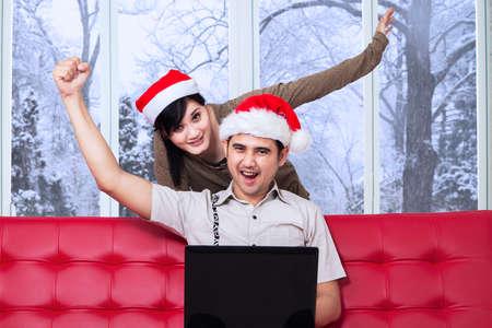 arbol geneal�gico: Pareja joven alegre que usa la computadora port�til para ir de compras en l�nea y expresar feliz mientras llevaba sombrero de navidad