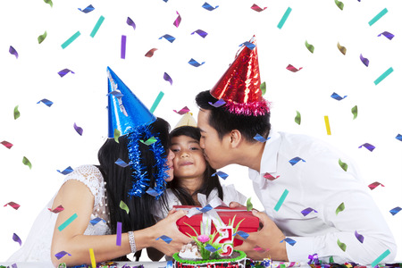 surprise party: Two asian parents celebrate child birthday and give a present while kiss their child