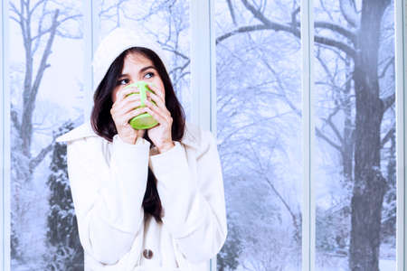 warm drink: Portrait of girl relaxed at home in winter holiday and enjoy a warm drink while wearing a winter coat