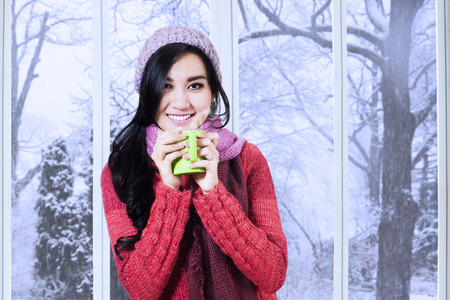 Portrait of woman smiling on the camera while enjoy a warm drink and wearing a knitted clothes at home photo