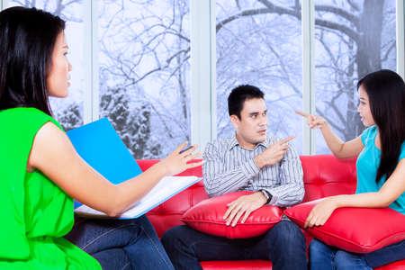 terapia psicologica: Psic�logo Mujer busca arbitrar sus pacientes durante la sesi�n de terapia psicol�gica Foto de archivo