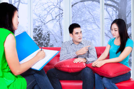 Female psychologist make a note during psychological therapy session photo