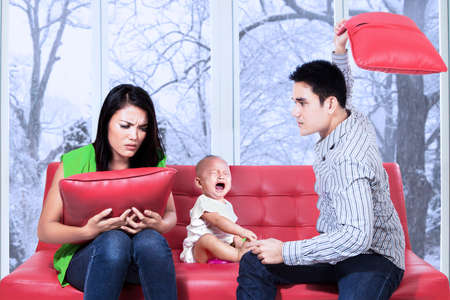 angry baby: Young asian man hitting his wife near their child and make the child crying Stock Photo