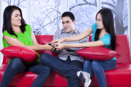 problemas familiares: Tres adolescente asiático sentado en el sofá y la lucha para tomar un mando a distancia con el fondo del invierno en la ventana