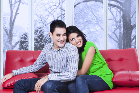 asian wife: Portrait of happy woman sitting on a red sofa and hugging boyfriend from the back Stock Photo