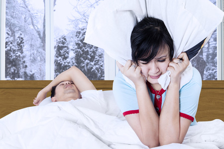 bed sheets: Portrait of young woman closed her ears with a pillow after hearing husband snoring