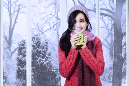 Portrait of young asian woman wearing a knitted clothes enjoy a warm drink at home photo