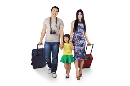 Three member of asian tourist walking in studio while carrying luggage Stock Photo