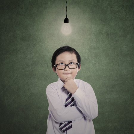 lit: Business boy is thinking under lit bulb in class Stock Photo