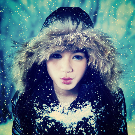 girl blowing: Beautiful asian girl wearing winter clothing with fur hood, blowing snow to the camera Stock Photo