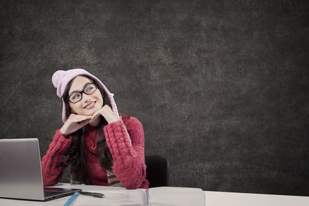 daydream: Portrait of pretty student daydream while studying in classroom and wearing warm clothes