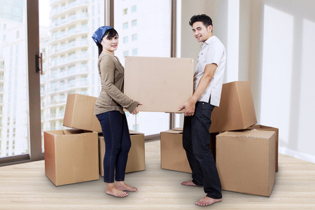 moving box: Young couple moving into new home carrying box
