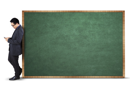 Hispanic businessman using smartphone and lean on empty blackboard for ad photo