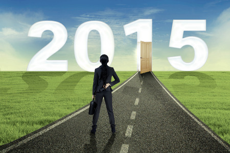Woman holding briefcase and standing on the road to future 2015 photo