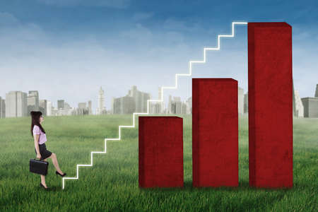 up stair: Businesswoman stepping up on the stair of business graph