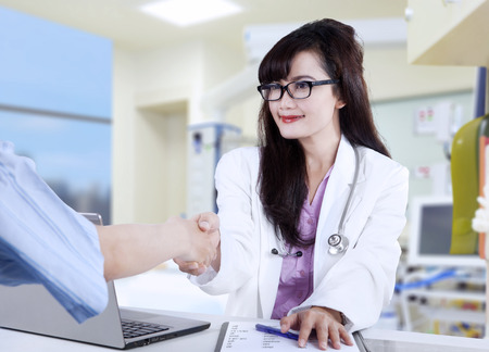 handshaking: Doctor shaking hands to patient in the office at desk