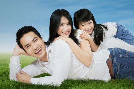 familias jovenes: Familia asiática feliz tumbado en la hierba y mirando a cámara, disparó al aire libre Foto de archivo