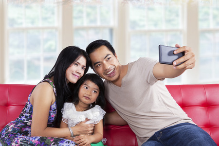 Cheerful family looking and smiling at camera phone when take a self portrait photo