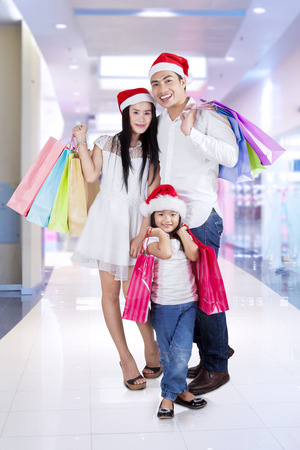 Three member of happy family carrying shopping bags and enjoy christmas sale photo