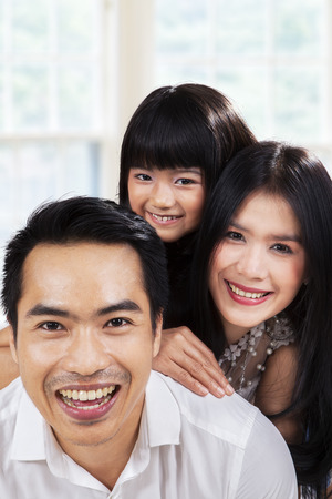 asian family home: Portrait of hispanic family smiling on camera at home