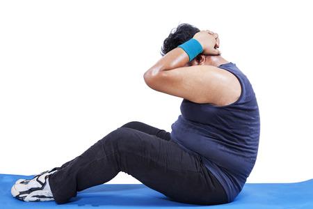 obesidad: Vista lateral del hombre que hace entrenamiento para bajar de peso en el estudio, aislado más de blanco